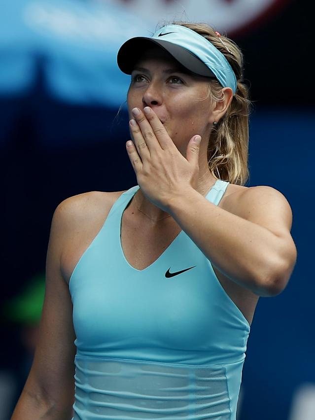 Maria Sharapova, left, of Russia blows kisses to the crowd after defeating Alize Cornet of France after winning their third round match at the Australian Open tennis championship in Melbourne, Australia, Saturday, Jan. 18, 2014.(AP Photo/Aaron Favila)