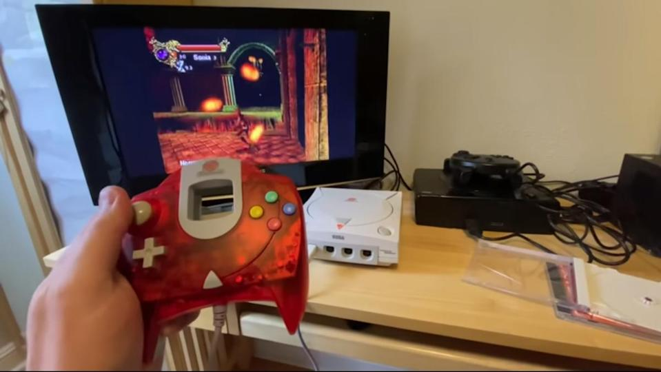 a hand holds a Sega Dreamcast remote while playing Castlevania Resurrection