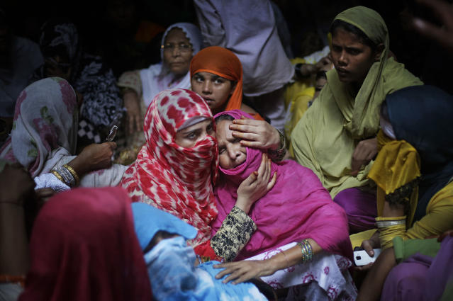<p>A woman comforts the mother of Shakil, 38, an Indian man killed by a gang on early Thursday night, near Jewar, 80km (50miles) south Delhi, India, May 25, 2017. Police are searching for a gang of highway robbers who allegedly raped four women after dragging them into a field and fatally shooting Shakil who tried to save them. The six looted cash and valuables from the family and then raped the women, the victims alleged. Violent crimes against women have been on the rise in India despite tough laws enacted by the government. (Photo: Altaf Qadri/AP) </p>