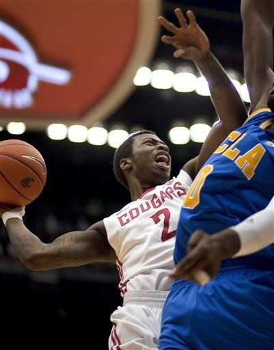 Washington State guard Mike Ladd (2) attempts a shot against UCLA center Anthony Stover (0) during the first half of an NCAA college basketball game on Saturday, Feb. 4, 2012, in Pullman, Wash. (AP Photo/Dean Hare)