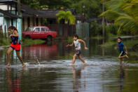 Children run in a flooded street caused by rains brought on by Hurricane Ida, in Guanimar, Artemisa province, Cuba, Saturday Aug. 28, 2021. (AP Photo/Ramon Espinosa)