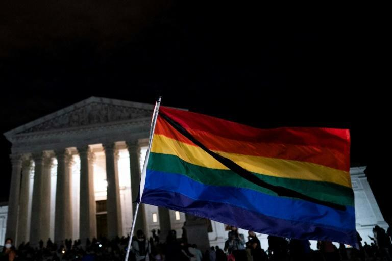 A rainbow flag waves as people gather near the steps of the Supreme Court buidling to pay tribute to Ruth Bader Ginsburg, who was known for her role in wideining LGBTQ rights