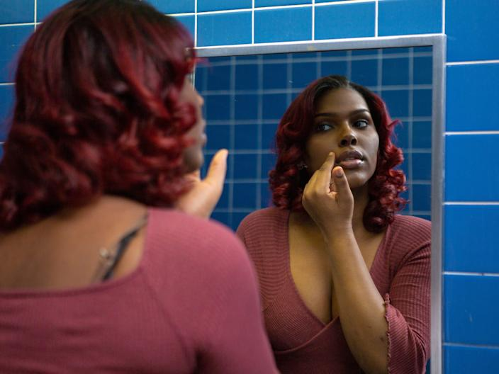 A young transgender woman looking at her face in the bathroom mirror at school