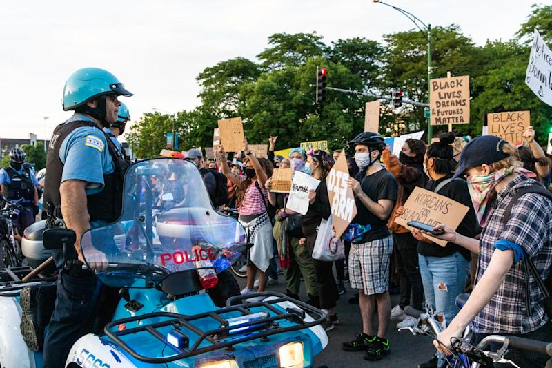 Protesters chant and wave signs at the Chicago Police Department during a protest: (2020 Getty Images)