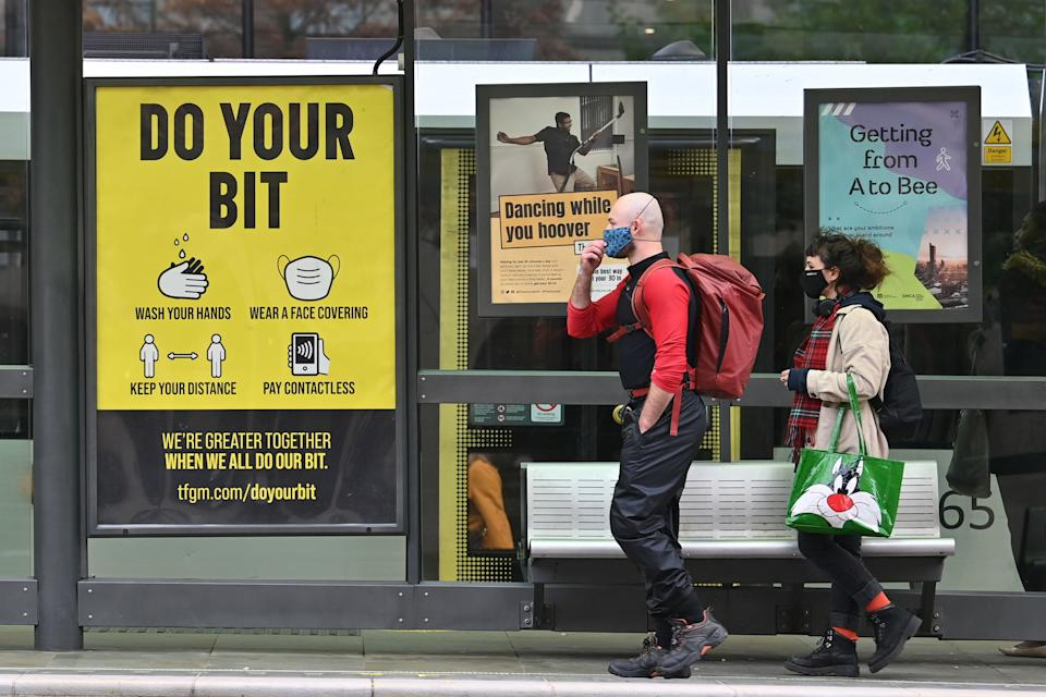 Pedestrians wearing face masks walk past a sign urging individuals to follow coronavirus guidelines at a tram stop in Manchester, northwest England as the country battles a surge in coronavirus cases on October 19, 2020 (Photo by Paul ELLIS / AFP) (Photo by PAUL ELLIS/AFP via Getty Images)
