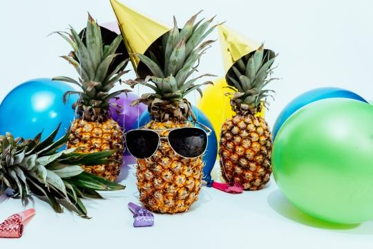 Pineapples with sunglasses and balloons having a party
