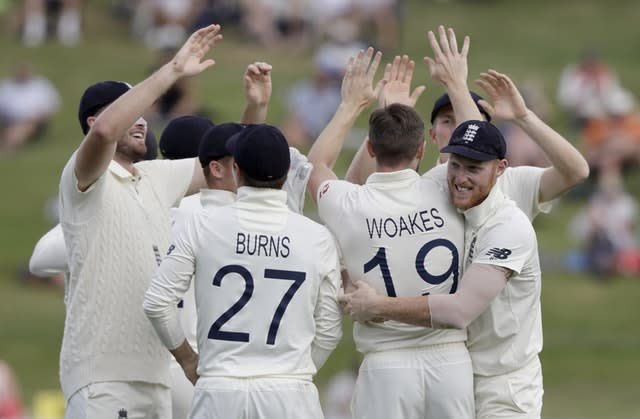 England players congratulate Chris Woakes after he took the wicket of New Zealand's Tom Latham (Mark Baker/AP)