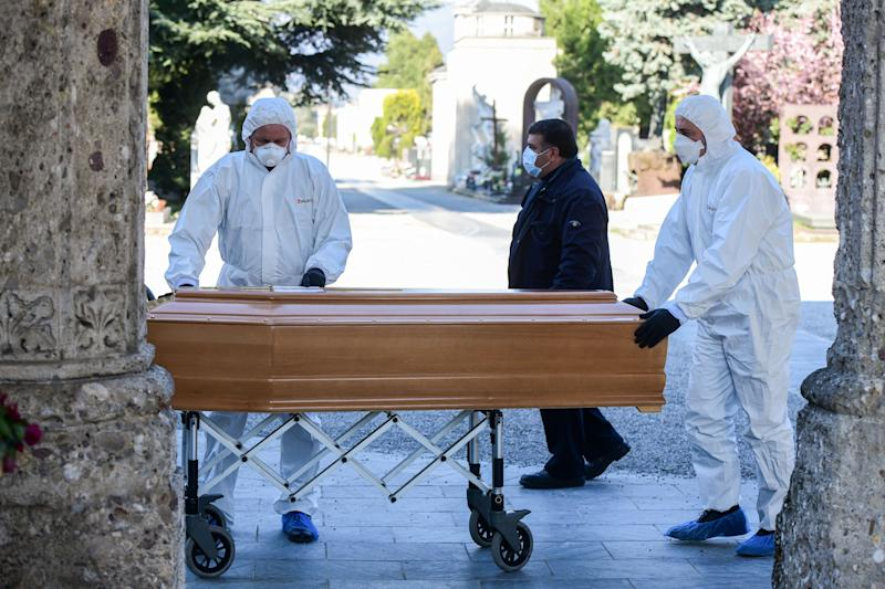 Undertakers wearing a face mask and overalls unload a coffin out of a hearse on March 16, 2020 at the Monumental cemetery of Bergamo, Lombardy, as burials of people who died of the new coronavirus are being conducted at the rythm of one every half hour. (Photo by Piero Cruciatti / AFP) (Photo by PIERO CRUCIATTI/AFP via Getty Images)