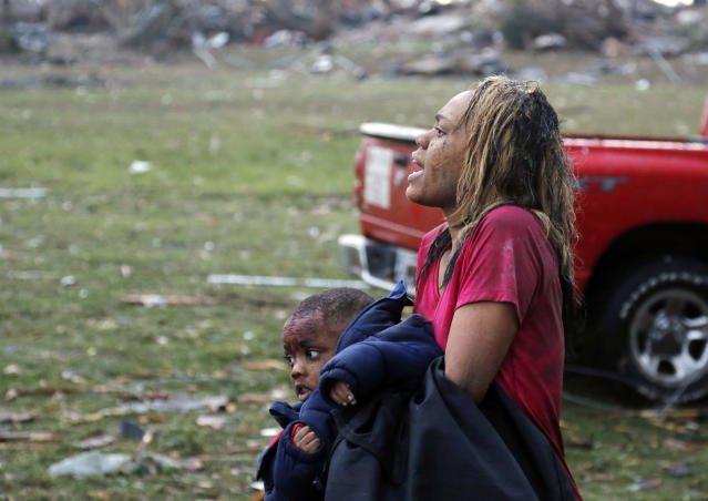 A woman carries an injured child to a triage center near the Plaza Towers Elementary School in Moore, Okla., Monday, May 20, 2013. A tornado as much as a mile (1.6 kilometers) wide with winds up to 200 mph (320 kph) roared through the Oklahoma City suburbs Monday, flattening entire neighborhoods, setting buildings on fire and landing a direct blow on an elementary school. (AP Photo/Sue Ogrocki)