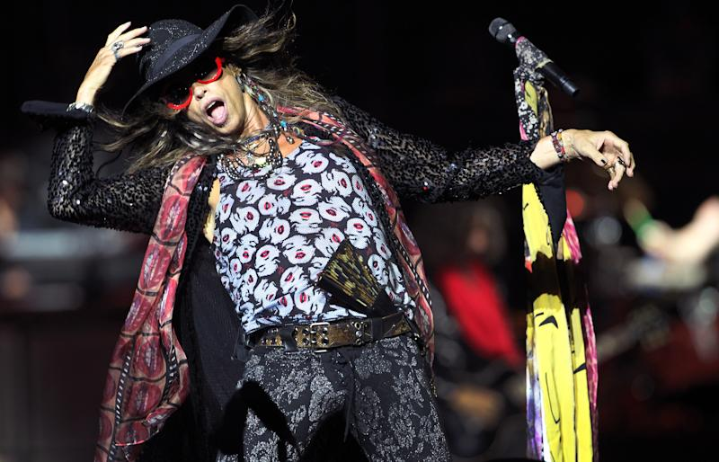 FILE - This May 25, 2013 file photo shows Steven Tyler, lead singer of American rock band Aerosmith performing in Singapore during the inaugural Social Star Awards concert. Aerosmith, James Taylor and Jimmy Buffett are joining other artists for a benefit concert for victims of the Boston Marathon bombings. Tickets for the show scheduled Thursday at the TD Garden sold out in minutes after they went on sale May 6. Proceeds will benefit One Fund Boston, the compensation fund established by Gov. Deval Patrick and Boston Mayor Thomas Menino to help those injured in the April 15 bombings and the families of three people killed.(AP Photo/Wong Maye-E, file)