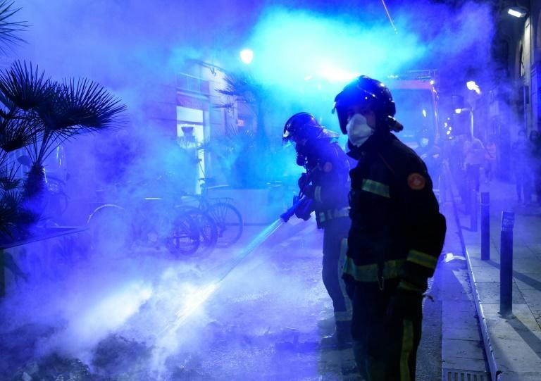 Firefighters put out a fire after a demonstration against a curfew in Barcelona as virus cases spike around Europe