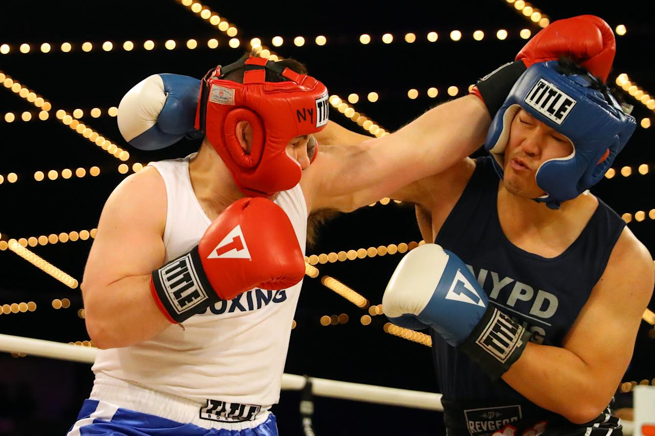 <p>Brian Fielder (red) exchanges punches with Brian Huang (blue) in the ring during a grudge match in the NYPD Boxing Championships at the Hulu Theater at Madison Square Garden on March 15, 2018. (Gordon Donovan/Yahoo News) </p>