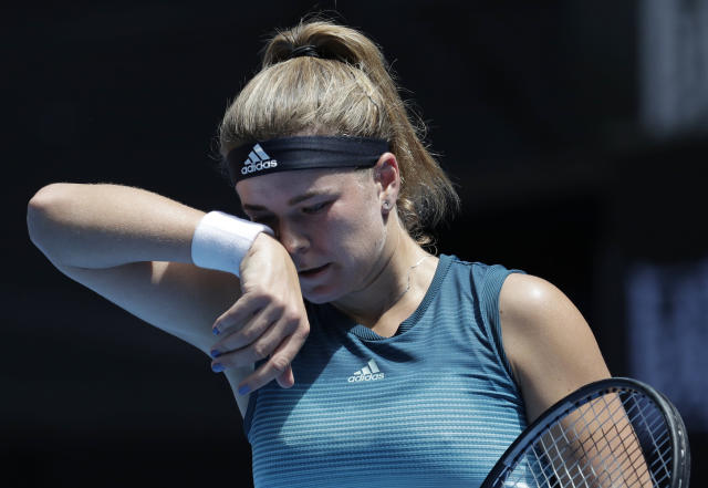 Karolina Muchova of the Czech Republic wipes the sweat from her face during her first round match against compatriot Karolina Pliskova at the Australian Open tennis championships in Melbourne, Australia, Tuesday, Jan. 15, 2019. (AP Photo/Aaron Favila)