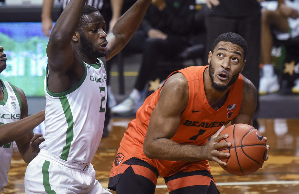 Oregon State guard Jarod Lucas (2) looks to shoot over Oregon forward Eugene Omoruyi during the first half of an NCAA college basketball game Saturday, Jan. 23, 2021, in Eugene, Ore. (AP Photo/Andy Nelson)