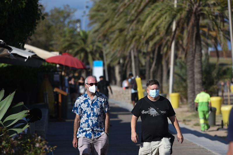 Tourists wearing face masks as a preventive measure walk along Somorrostro beach during the coronavirus crisis. (Photo: SOPA Images via Getty Images)