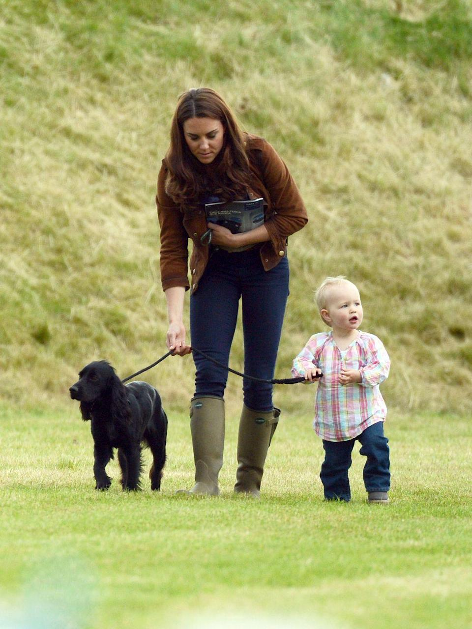 <p>The Duchess of Cambridge walks her dog, Lupo, with a 2-year-old Savannah Phillips. When Savannah was born in 2010, she was the first great-grandchild for Queen Elizabeth. </p>