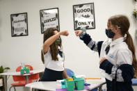 Students Sofia Senra, left, and Emma Orell, right, bump fists as they work on a lesson together at iPrep Academy on the first day of school, Monday, Aug. 23, 2021, in Miami. Schools in Miami-Dade County opened Monday with a strict mask mandate to guard against coronavirus infections. (AP Photo/Lynne Sladky)