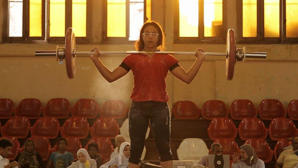 """<p>Bringing true meaning to the phrase """"fly-on-the-wall,"""" Mayye Zayed's documentary spotlights the world of female weightlifting in Alexandria, Egypt, and the trials and tribulations faced by one team in their bid for success. Captain Ramadam is their leader, a former champion weightlifter who has trained up some of Egypt's finest athletes to compete and succeed at Olympic level. His latest protégée is 14-year-old Zebibi, and over four years we see her grow-up and face mounting pressure from her aging coach as he struggles to get funding to improve his dilapidated gym.</p><p>It's an empowering film to show the obstacles women face to compete at the highest levels, especially in countries where they're still dealing with gender and economic inequality. By assimilating the camera's eye into the team and allowing the subjects to push the narrative forward as they train and contend with the complex bonds that bind them together, Zayyed serves up a human interest story of sincere heart and honesty.</p>"""