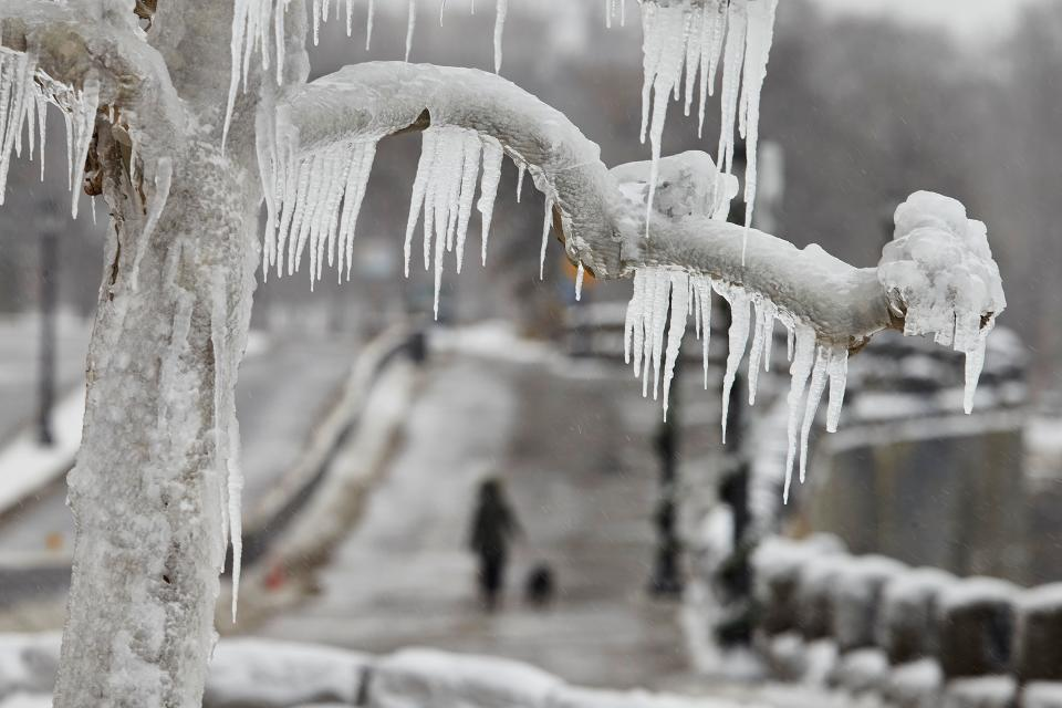 A woman walks her dog in the distance, along the Niagara Parkway in Niagara Falls, Ontario, on January 27, 2021. (Photo by Geoff Robins / AFP) (Photo by GEOFF ROBINS/AFP via Getty Images)