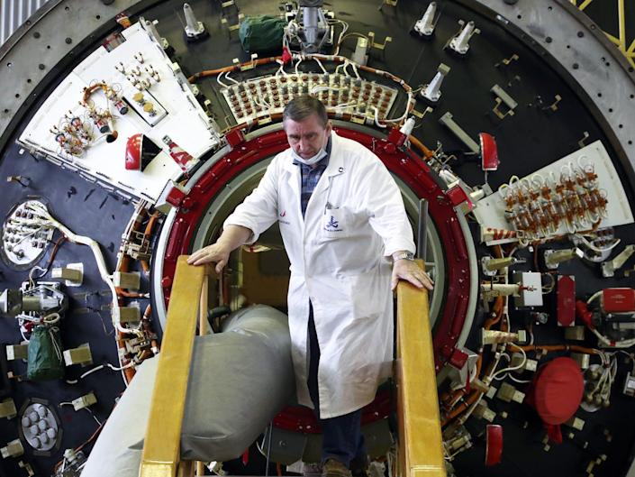 man in white lab coat stands in front of nauka module port opening in lab room