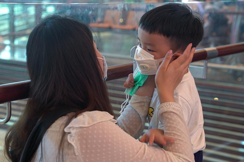 A woman wearing a mask helps her son put on his mask at Changi Airport here on 25 January, 2020. (PHOTO: Getty Images)