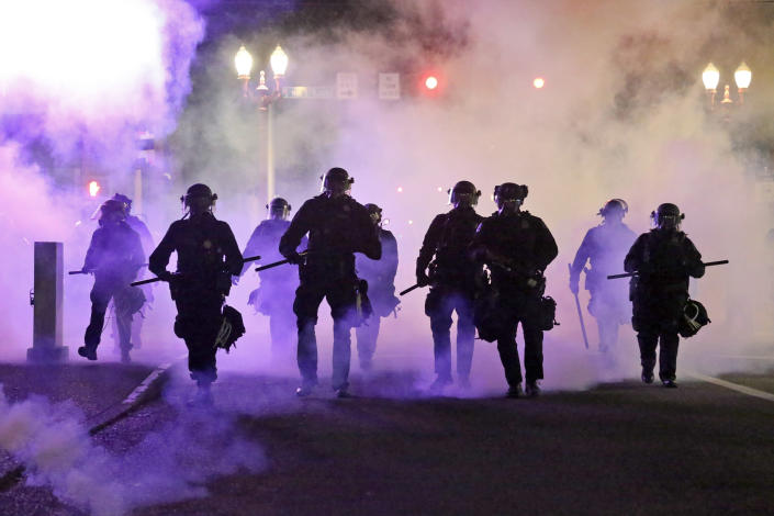 FILE - In this March 29, 2020, file photo, police officers walk enveloped by tear gas in Portland, Ore. City commissioners in Portland voted Wednesday, June 17, 2020 to cut nearly $16 million from the Portland Police Bureau's budget in response to concerns about police brutality and racial injustice. The cuts are part of a city budget approved by the commissioners by a 3-1 vote in a contentious meeting.(Dave Killen/The Oregonian via AP, File)