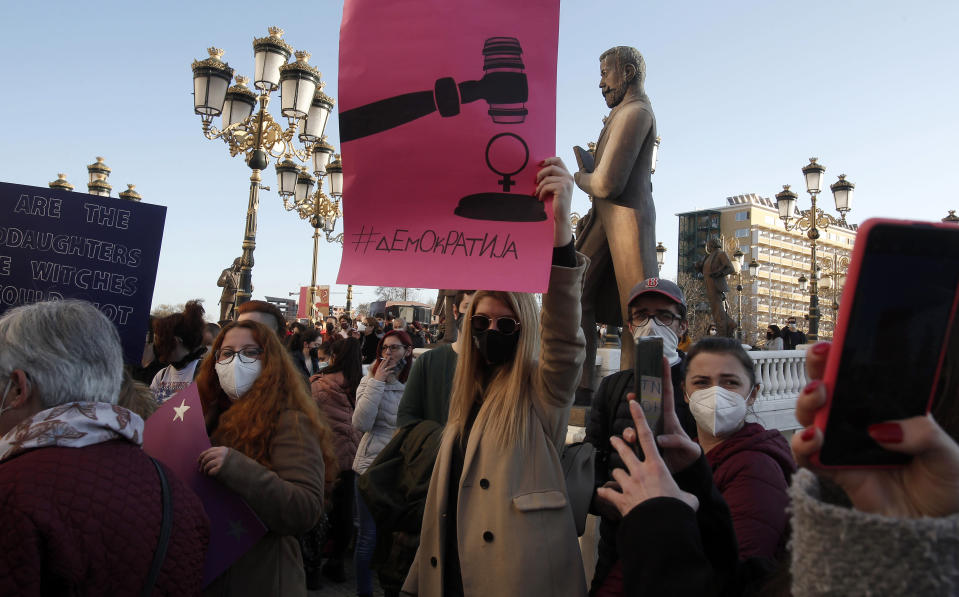 """Young people wearing face masks carry banners during a protest march through downtown Skopje, North Macedonia, on Wednesday, Feb. 3, 2021. Several hundred mostly young people have gathered in front of the North Macedonia's Interior ministry on Wednesday to protest sexual harassment of women on social media and policy of impunity for that kind of violence. The banner reads in Macedonian """"#Democracy""""(AP Photo/Boris Grdanoski)"""