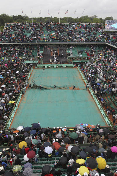 Stadium employees cover center court as the mens final match between Rafael Nadal of Spain and Novak Djokovic of Serbia was suspended because of the rain at the French Open tennis tournament in Roland Garros stadium in Paris, Sunday June 10, 2012. (AP Photo/David Vincent)