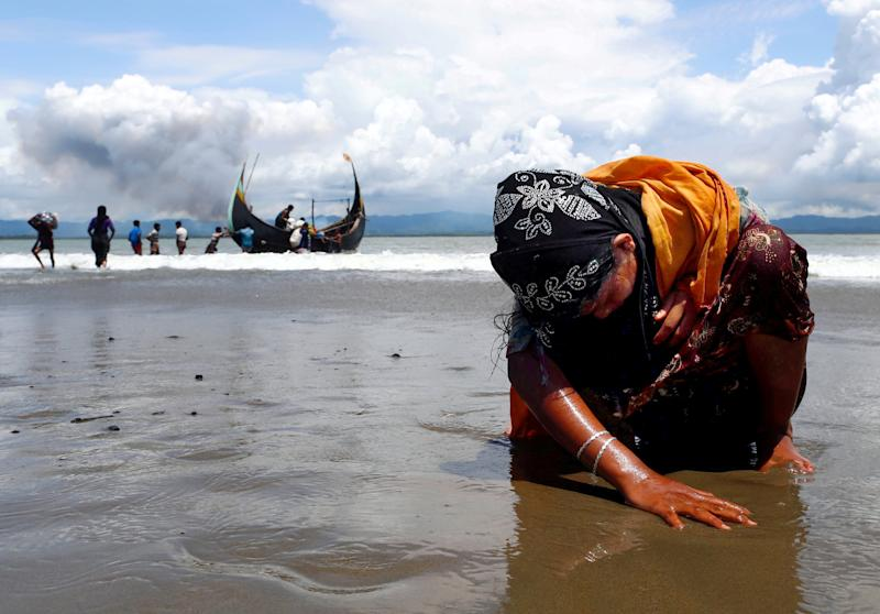 An exhausted Rohingya refugee woman touches the shore after crossing the Bangladesh-Myanmar border by boat on Sept. 11, 2017. (Danish Siddiqui/Reuters)