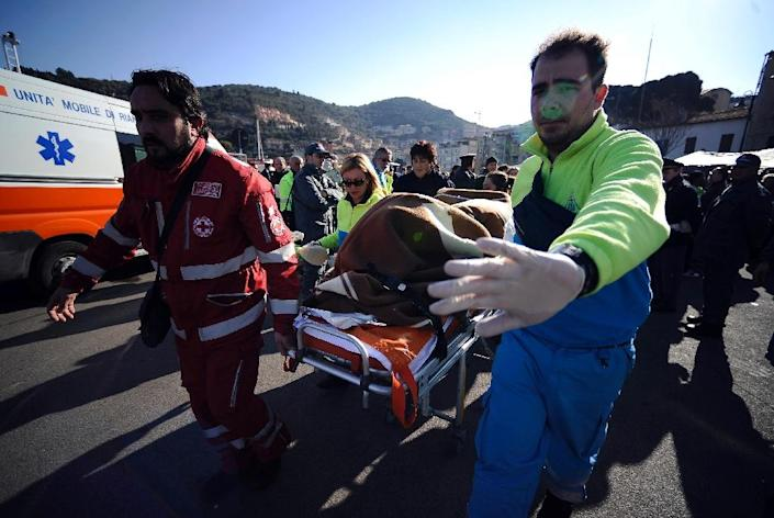 Medics carry a Costa Concordia passenger on a stretcher at Porto Santo Stefano, on January 14, 2012, after the cruise ship with more than 4,000 people on board capsized (AFP Photo/Filippo Monteforte)