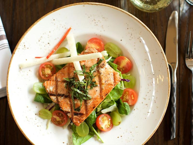 Virtuous food options, like grilled Alaskan king salmon with tomato, grape, and basil, are par for the course on Holland America's cruises. | Julie Ellis/Holland America Line