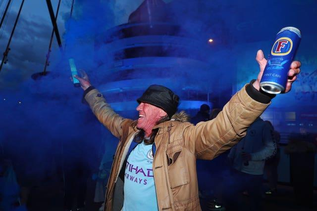 A jubilant Manchester City fan celebrates his club regaining the Premier League title by lighting a flare outside the Etihad Stadium. City were confirmed champions on May 11 after second-placed Manchester United were beaten 2-1 at home by Leicester. Glory for Pep Guardiola's side, who are set to lift the trophy in front of 10,000 supporters after hosting Everton on Sunday, was their third title success in four seasons