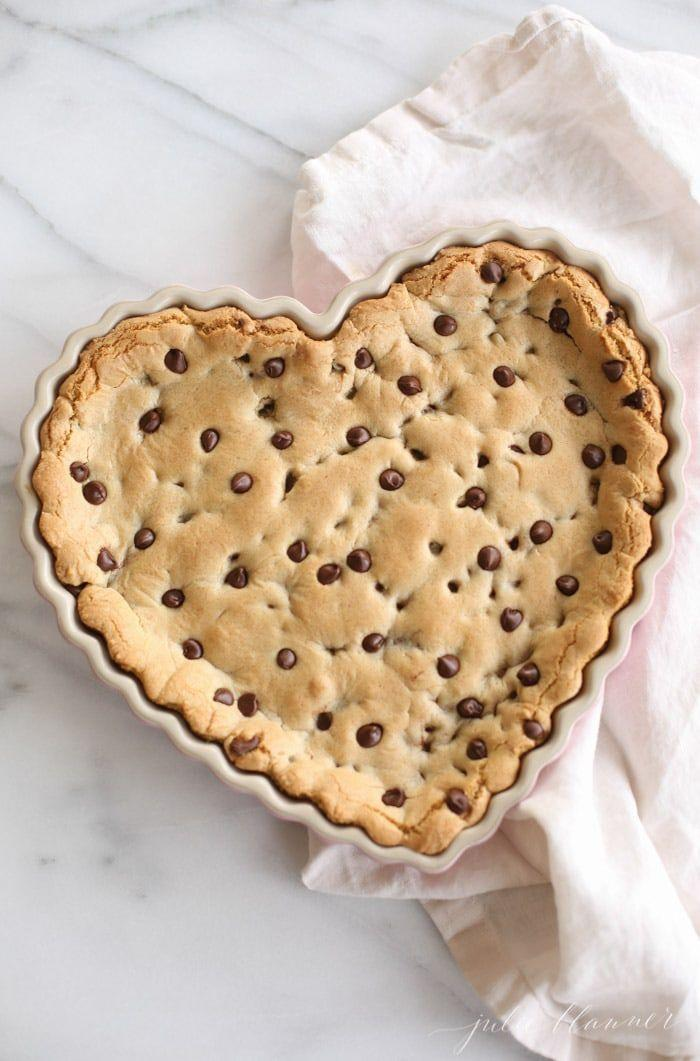 """<p>You wear your heart on your sleeve, and now you can put it on the dessert table for all to see. Bake his favorite cookie in a heart-shaped pan and decorate with the toppings of his choice. </p><p><em><a href=""""https://julieblanner.com/chocolate-chip-cookie-cake-recipe/"""" rel=""""nofollow noopener"""" target=""""_blank"""" data-ylk=""""slk:Get the recipe from Julie Blanner »"""" class=""""link rapid-noclick-resp"""">Get the recipe from Julie Blanner »</a></em></p>"""