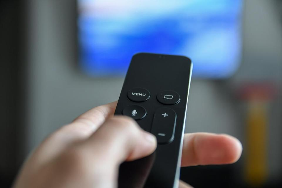 Man using remote control to switch channels. Close up hand holding big screen tv remote.