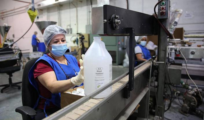 Due to the coronavirus pandemic Toast distillers began partnering with Cosmetic Corp. an FDA approved lab in Medley, to use their alcohol to produce hand sanitizer. On Tuesday, June 23, 2020, Alina Gonzalez places labels on large jars of the EZ Hand Sanitizer as it moves down the production line at the facility inside of the Cosmetic Corp. building.