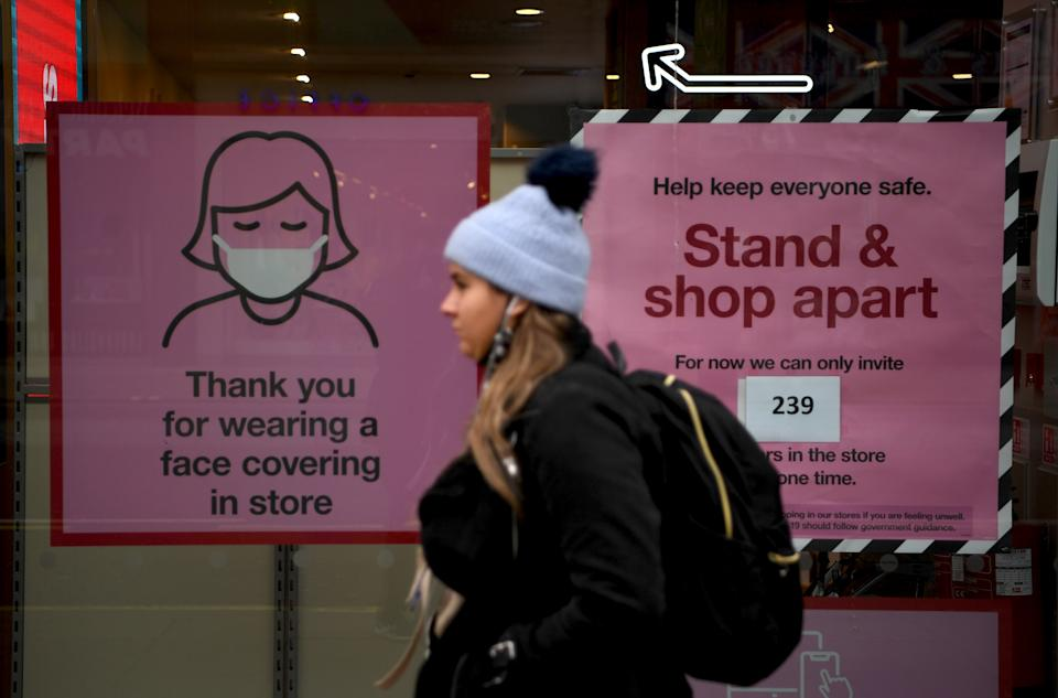 A pedestrian walks past posters advising customers to wear a face mask or covering due to the COVID-19 pandemic, as she walk past a temporarily closed-down shop on an almost deserted Oxford Street in London on November 26, 2020. - Britain's government on Wednesday unveiled plans to slash the foreign aid budget to help mend its coronavirus-battered finances, prompting one minister to quit and defying impassioned calls to protect the world's poorest people. (Photo by DANIEL LEAL-OLIVAS / AFP) (Photo by DANIEL LEAL-OLIVAS/AFP via Getty Images)