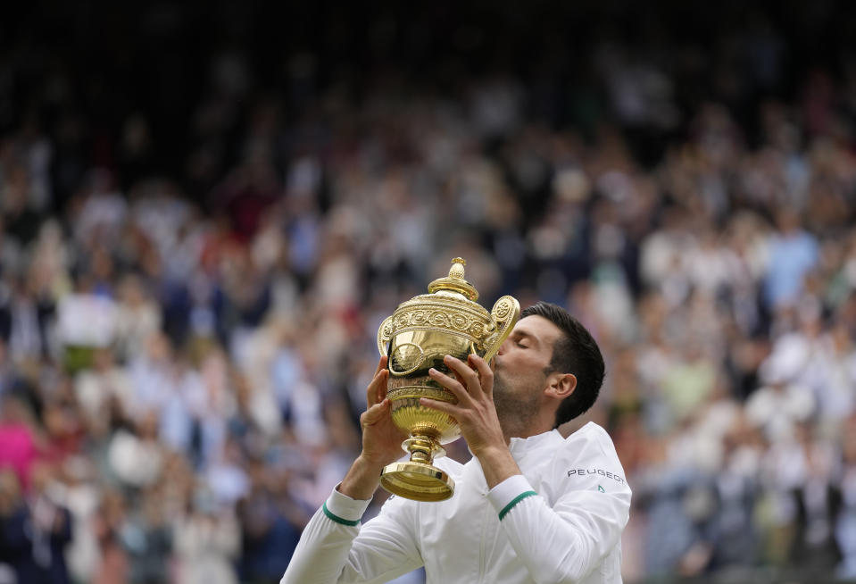 Serbia's Novak Djokovic kisses the winners trophy as he poses for photographers after he defeated Italy's Matteo Berrettini in the men's singles final on day thirteen of the Wimbledon Tennis Championships in London, Sunday, July 11, 2021. (AP Photo/Kirsty Wigglesworth)
