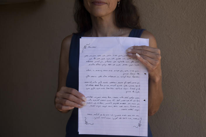 Idit Harel Segal, who donated a kidney to a Palestinian child from the Gaza Strip, holds with the letter she wrote to the boy, handwritten in Hebrew before giving him an Arabic translation, in her home in Eshhar, northern Israel, Tuesday, July 13, 2021. (AP Photo/Maya Alleruzzo)