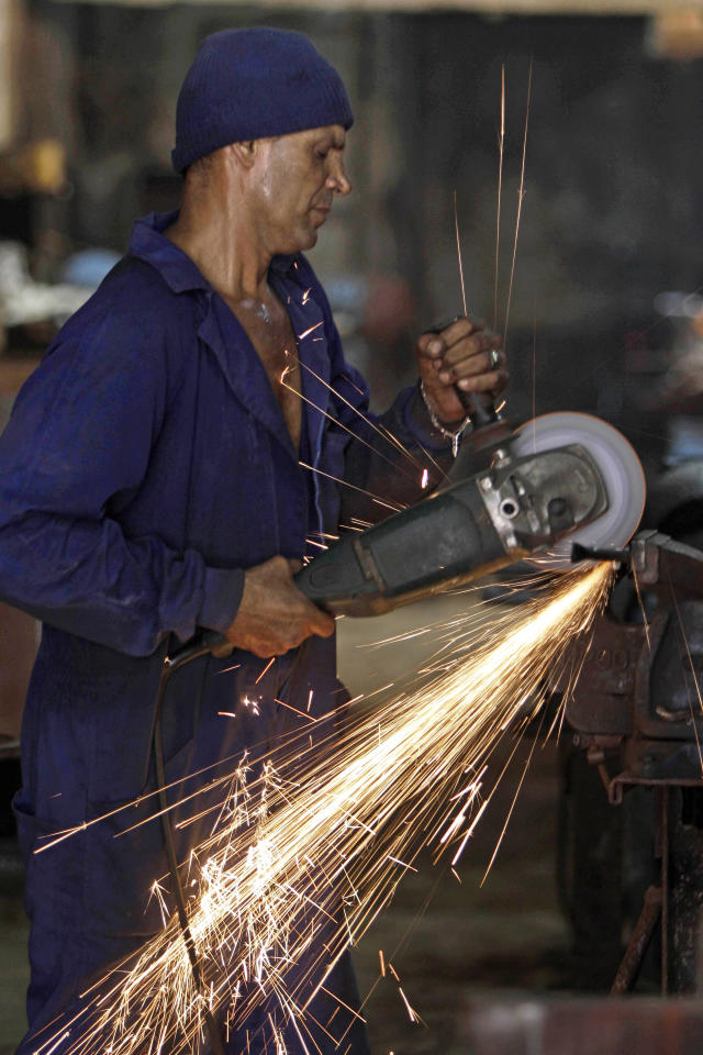 In this May 25, 2012 photo, Felix Guirola cuts an iron bar as he builds a bicycle that he says will measure 5.5 meters (18 feet) tall as he works on it at a friend's iron workshop in Havana, Cuba. Guirola has been riding tall since 1983, when seeing a tandem bike inspired him to build up instead of out. He said his first tall bike measured 5.3 feet (1.6 meters), and they got progressively taller until five years later he was riding 18 feet (5.5 meters) in the air at Ciego de Avila carnivals. (AP Photo/Franklin Reyes)