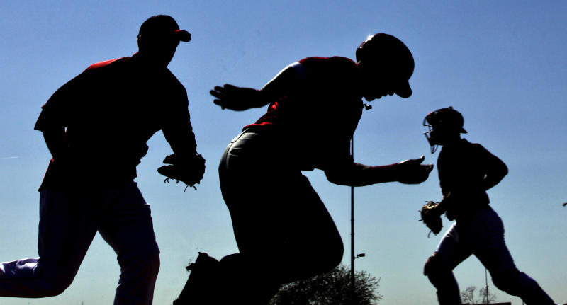 Los Angeles Angels players run a drill during a spring training baseball workout Friday, March 2, 2012, in Tempe, Ariz. (AP Photo/Morry Gash)