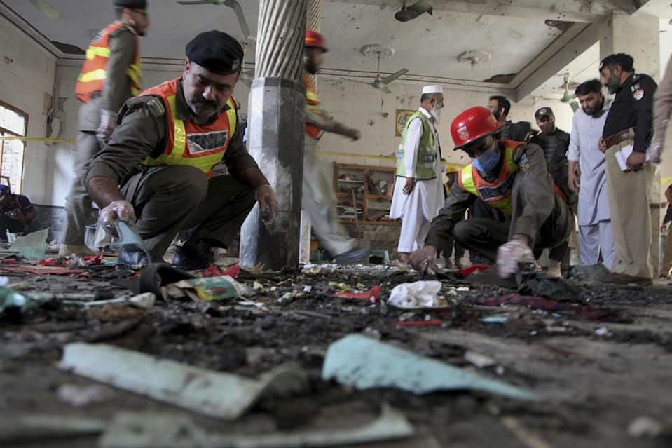 Rescue workers and police officers examine the site of the bomb explosion in an Islamic seminary in Peshawar: AP