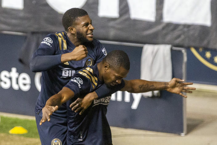 Philadelphia Union's Mark McKenzie, top, leaps upon teammate Cory Burke after he scored the go-ahead and eventual game-winning goal against the Chicago Fire during the second half of an MLS soccer match, Wednesday, Oct. 28, 2020, at Subaru Stadium in Chester, Pa. (Charles Fox/The Philadelphia Inquirer via AP)