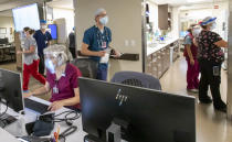 In this Thursday, Aug. 19, 2021, photo, the staff works inside the Emergency Department at Asante Three Rivers Medical Center in Grants Pass, Ore. The staff has seen a higher patient load than any time in the past year, attributable to the surge of patients suffering from COVID-19. One nurse said they hit the floor running and are slammed their entire shift. The hospitalization rate of unvaccinated COVID-19 is breaking records and squeezing hospital capacity, with several running out of room to take more patients. (Mike Zacchino/KDRV via AP, Pool)