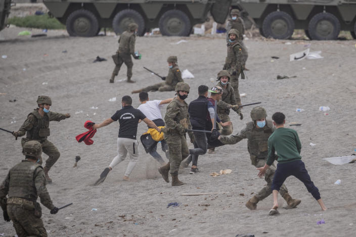 Spanish Army soldiers clash with migrants near the border of Morocco and Spain, at the Spanish enclave of Ceuta, on Tuesday, May 18, 2021. Ceuta, a Spanish city of 85,000 in northern Africa, faces a humanitarian crisis after thousands of Moroccans took advantage of relaxed border control in their country to swim or paddle in inflatable boats into European soil. (AP Photo/Bernat Armangue)