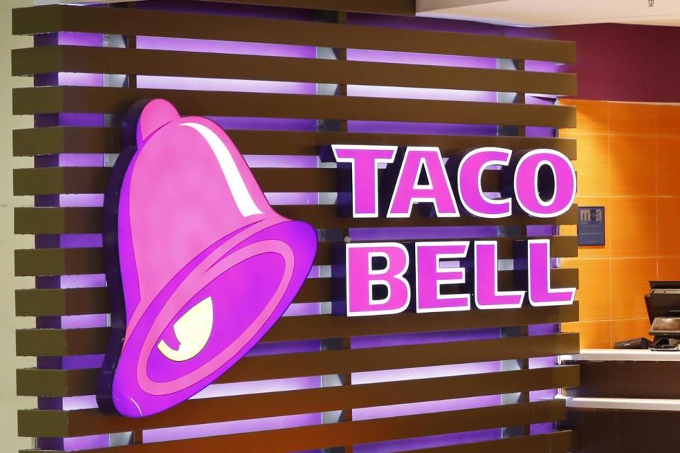"""FILE - This Friday, April 19, 2019 photo shows a Taco Bell logo at a restaurant in Miami. On Friday, March 26, 2021, The Associated Press reported on social media posts circulating online incorrectly asserting Taco Bell is offering $60 and Walmart is offering $75 coupons to customers who share and comment on their posts. The posts come from Facebook accounts that at first glance appear to match the name and branding of each company, but actually claim to represent an """"unofficial community page."""" Representatives from both companies confirmed the posts are not real. (AP Photo/Wilfredo Lee)"""