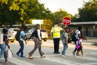 Parents and children arrive at Egypt Lake Elementary School for the first day of school for Hillsborough County students, Tuesday, Aug. 10, 2021 in Tampa. (Martha Asencio-Rhine/Tampa Bay Times via AP)