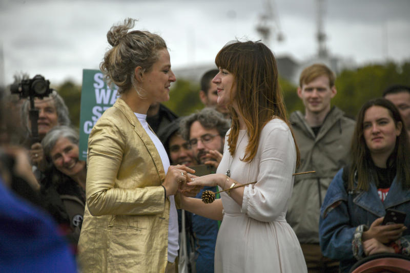 Two women celebrate their marriage on Westminster Bridge, during an Extinction Rebellion protest in London, Monday, Oct. 7, 2019. London Police say some 135 climate activists have been arrested as the Extinction Rebellion group attempts to draw attention to global warming. Demonstrators playing steel drums marched through central London on Monday as they kicked off two weeks of activities designed to disrupt the city. (AP Photo/Alberto Pezzali)