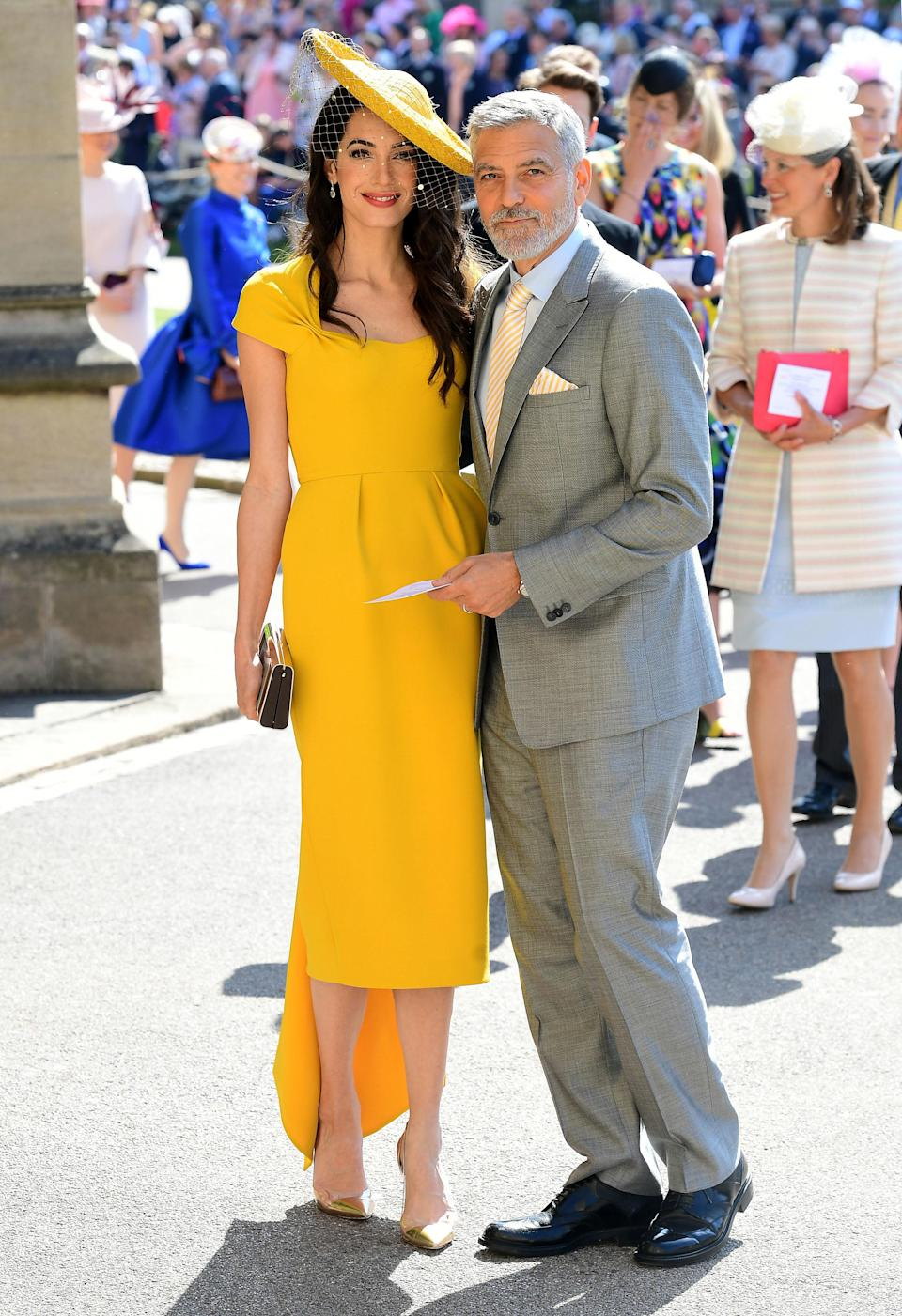 <p>Easily the best dressed couple so far, don't you agree? Amal's wearing a yellow Stella McCartney look with a hat by Stephen Jones. <em>[Photo: PA]</em> </p>