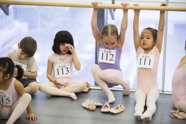 Children play on bars while waiting for their turn during an audition for the School of American Ballet in New York April 25, 2014. The school is holding auditions for over 600 beginner ballet students, who will be selected to fill the 120 spots available to study on campus. REUTERS/Lucas Jackson (UNITED STATES - Tags: SOCIETY EDUCATION)