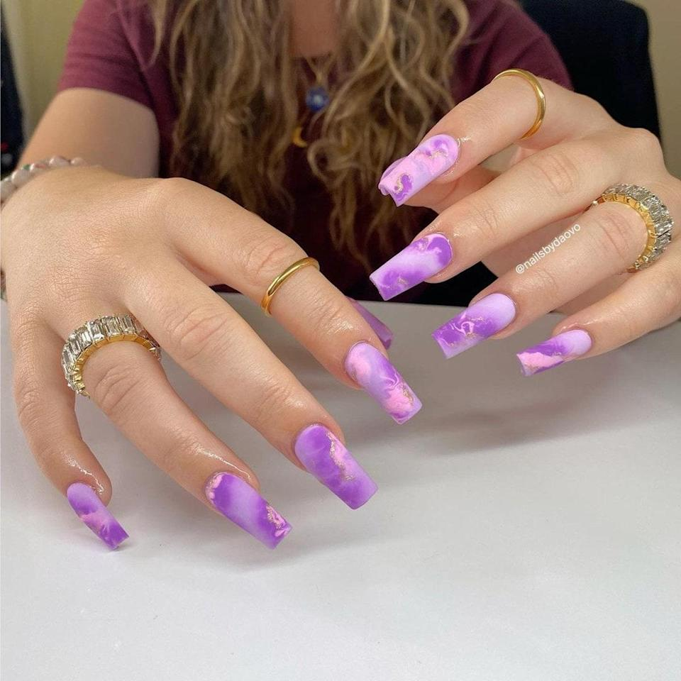 """This swirly, purple, square-shaped manicure was carved by Los Angelos manicurist <a href=""""https://www.instagram.com/nailsbydaovo/"""" rel=""""nofollow noopener"""" target=""""_blank"""" data-ylk=""""slk:Đaô Vo"""" class=""""link rapid-noclick-resp"""">Đaô Vo</a>. Vo used <a href=""""https://www.allure.com/story/blooming-gel-nail-art-trend?mbid=synd_yahoo_rss"""" rel=""""nofollow noopener"""" target=""""_blank"""" data-ylk=""""slk:blooming gel"""" class=""""link rapid-noclick-resp"""">blooming gel</a> to create this gorgeous marble effect. If you look closely, you'll notice tiny ripples of gold glitter that almost look like bolts of lightning in clouds."""